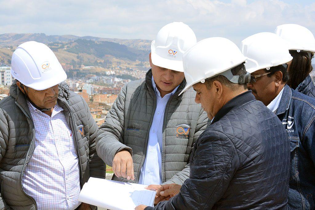 equipo de ingenieros mirando los planos de la obra